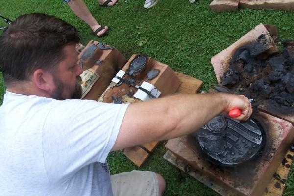 Sculptor Karl Unnasch opens a sand-block mold to unveil a Discover Sculpture Explore Lanesboro medallion.