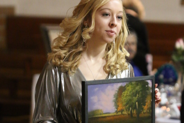 Former Lanesboro Arts intern, LeiLani Oas, displays a painting in the live auction at Swingsation 2013.